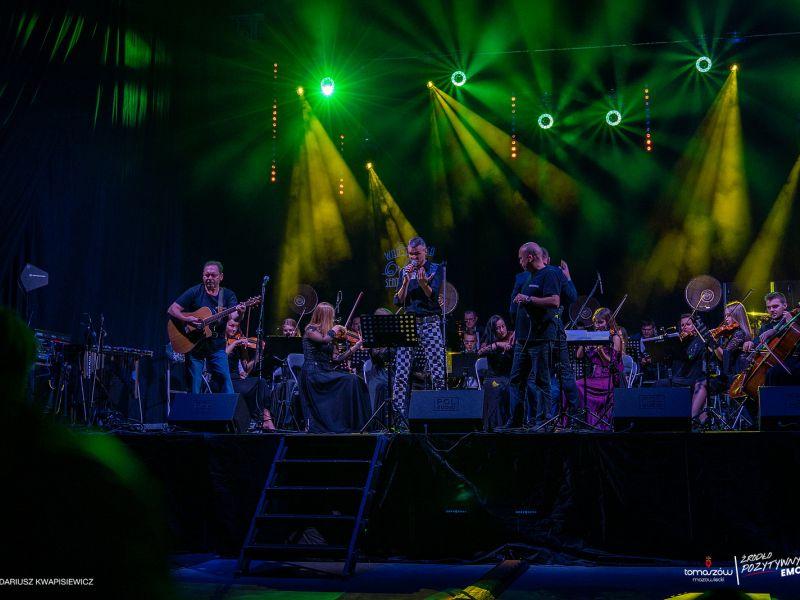 Scena, na niej orkiestra symfoniczna, mężczyźni, zielone światła