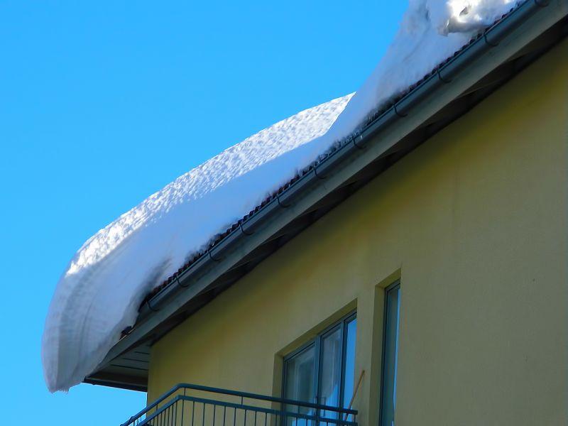 Na zdjęciu budynek mieszkalny z dachem, na którym wisi zaspa śnieżna. Budynek w kolorze żółtym z fragmentem balkonu, zwisający śnieg z dachu po świeżych opadach