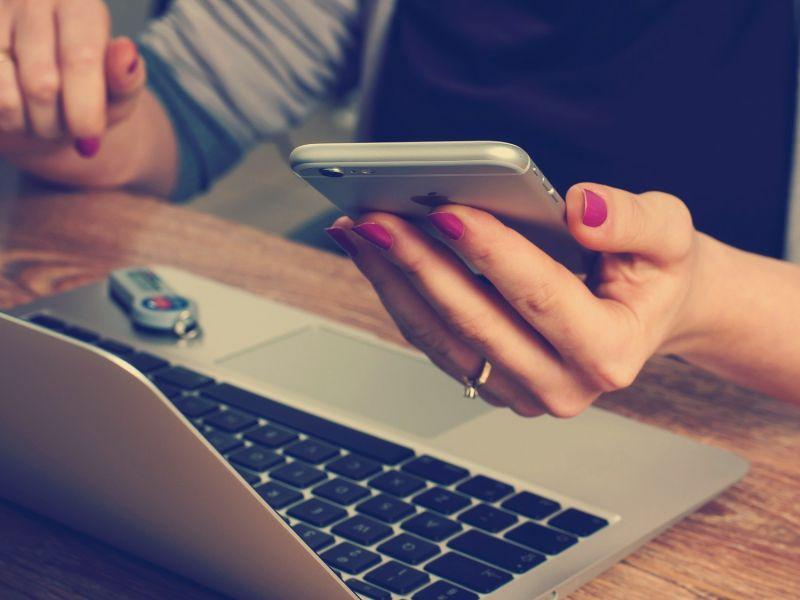 Na zdjęciu ręce osoby trzymającej ręce na klawiaturze laptopa, w drugim ręku trzymającej telefon komórkowy