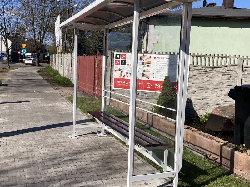 Na zdjęciu nowa wiata przystankowa zlokalizowana na ul. Popiełuszki. Wuiata oszklona z ławeczką drewnianą