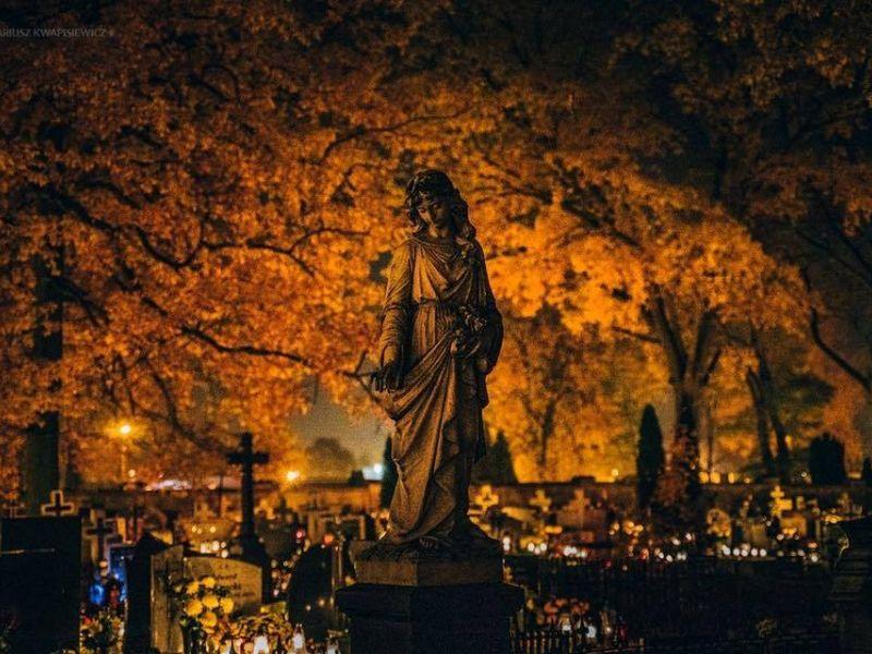 Na zdjęciu widać cmentarz w porze wieczornej, na pierwszym planie figura młodej kobiety na nagrobku, w tle panorama cmentarza ze zniczami (zapalonymi) i krzyżami