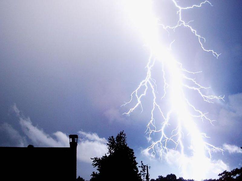 Ciemne, granatowe niebo, widoczny ciemny zaryzs budnku, niebo przecina jasna błyskawica