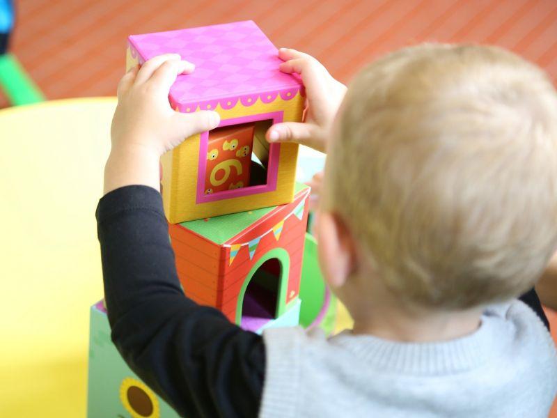 Na zdjęciu widać małe dziecko siedzące tyłem i bawiące się klockami