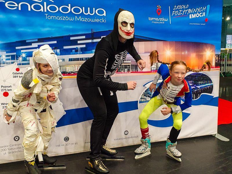 Na zdjęciu widać osoby na łyżwach w przebraniach z okazji Halloween. W tle baner Areny lodowej w Tomaszowie Mazowieckim. Na zdjęciu dorosła łyzwiarka w stroju kościotrupa i dwójka dzieci przebranych za mumię i młodego kościotrupa