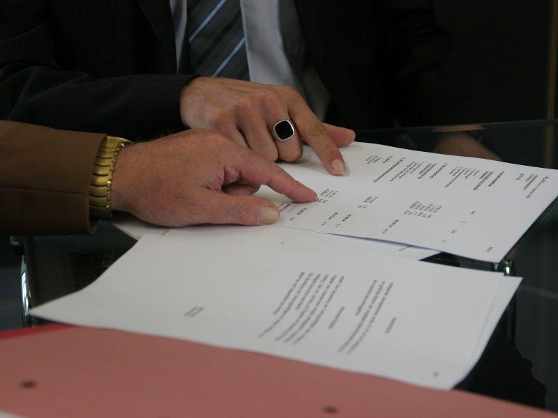 Na zdjęciu widać dwie dłonie męskie, wskazują coś na rozłożonych na stoliku dokumentach