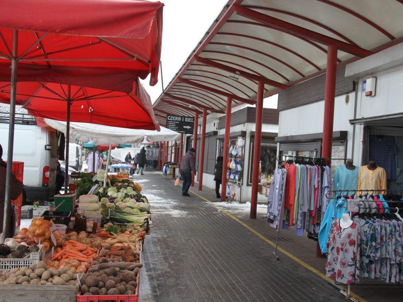 Na zdjęciu fragment targowiska miejskiego przy placu Narutowicza. Na fotografii widać stragany kupieckie z warzywami i odziezą oraz fragment zadaszenia