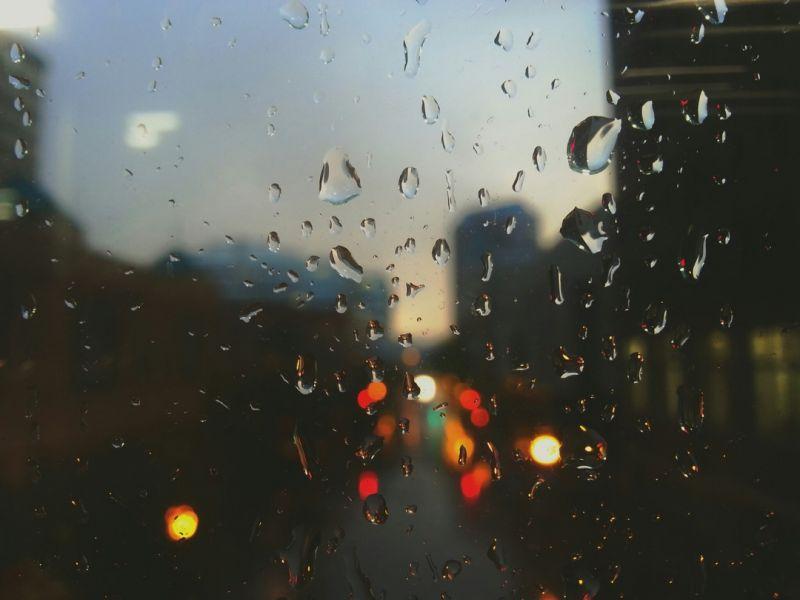 Na zdjęciu widać krople spływające po szybie, w tle rozmazane światła miasta