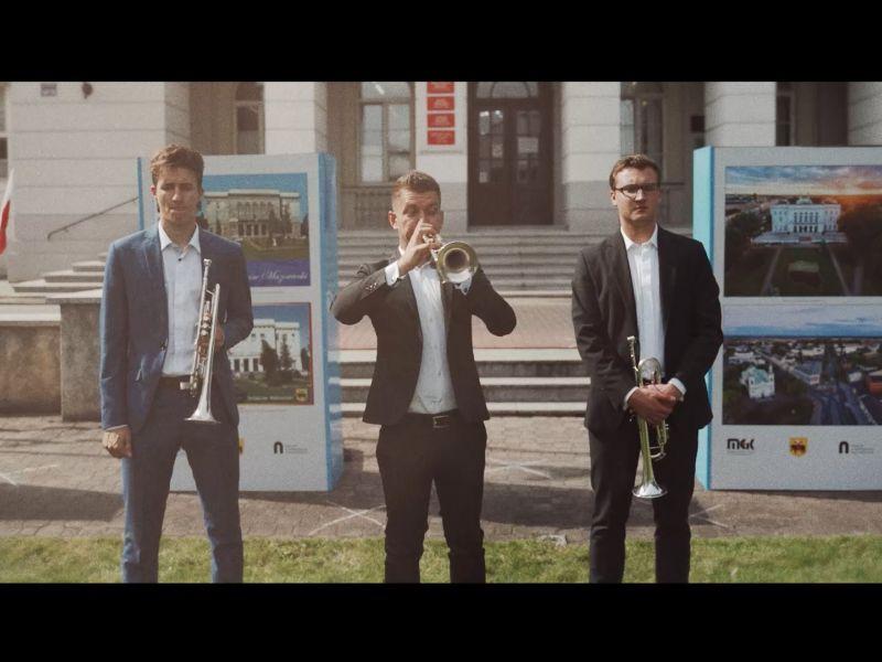 Na zdjęciu trzech muzyków, trębaczy, wykonujących hejnał Tomaszowa Mazowieckiego. W tle budynek Urzędu Miasta i widoczny fragment wystawy o historii miasta