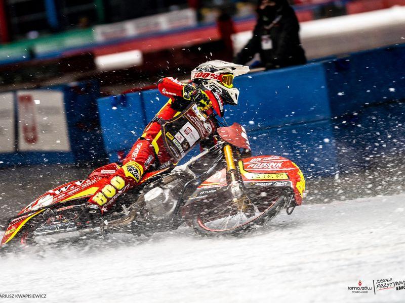 Na fotografii motocyklista podczas wyścigu na lodzie. Motocyklista ubrany w czerwony kombinezon podczas brania ostrego zakrętu. Wokół rozbryzgi lodu.