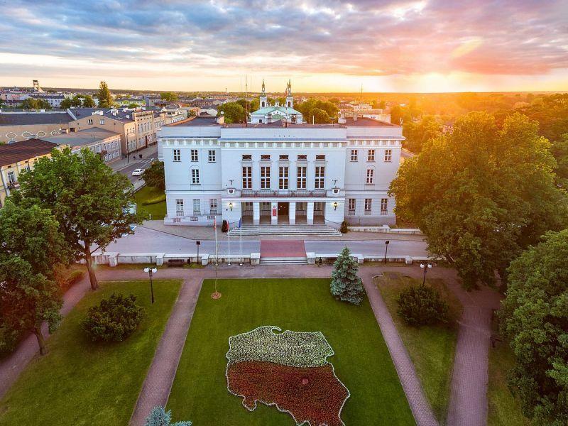Na zdjęciu budynek Urzędu Miasta widok z góry. Widać gmach obiektu oraz trawnik z konturami Polski