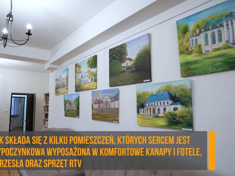 Ściana z obrazmi oraz napis: budynek składała się z kilku pomieszczeń, których sercem jest sala wypoczynkowa wyposażona w komfortowe kanapy i fotele, stoły, krzesła oraz sprzęt RTV
