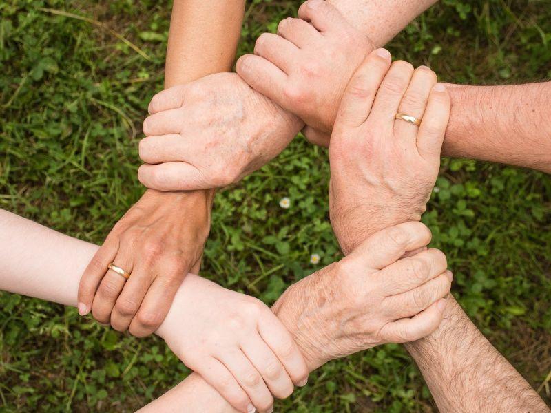 Na zdjęciu widok rąk, które wzajemnie są splecione. Jedna ręka trzyma inną rękę i sama jest trzymana przez kolejną rękę.