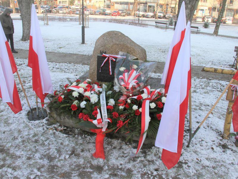 Na zdjęciu obelisk poświęcony Powstańcom Listopadowym zlokalizowany na Skwerze Powstańców, pod którym zostały złozone wiązanki kwiatów. Obelisk w otoczeniu flag narodowych