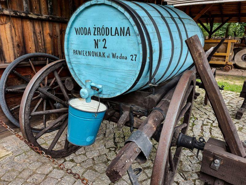 Na zdjęciu zrekonstruowany beczkowóz. Pomalowana na niebiesko beczka na wozie na drewnianych kołach