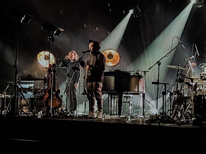 Na zdjęciu widać mężczyznę na scenie przy mikrofonie. Za nim widać instrumenty: fortepian, perkusja, gitara oraz muzyka towarzyszącego.