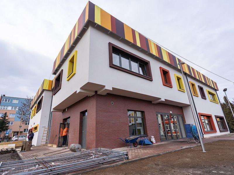 Na zdjęciu bryła budynku nowego żlobka w Tomaszowie Mazowieckim. Na fotografii widac budynek i teren przed budynkiem w trakcie prac porządkowych