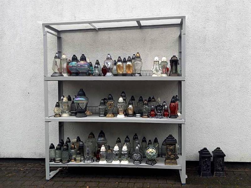 zdjęcie przedstawia stalowy regał z trzema półkami na którym stoją szklane znicze