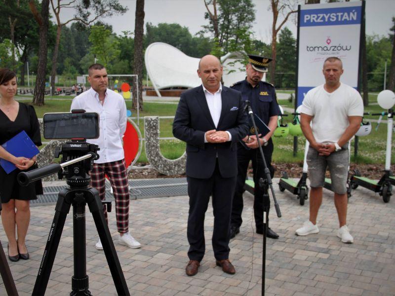 Na zdjęciu prezydent miasta, przedstawiciele firmy udostepnijącej usługę e-hulajnogi i komendant Straży Miejskiej oraz rzecznik miasta podczas konferencji na przystani miejskiej. W tle amfiteatr