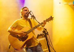 Na zdjęciu Paweł Domagała podczas koncertu w Tomaszowie Mazowieckim. Artysta w żółtej koszullce, gra na akustycznej gitarze i śpiewa do mikrofonu