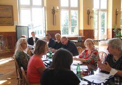 Na zdjęciu, przy długim stole siedzi 10 osób - rozmawiają