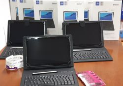 Na zdjęcoi widać 3 tablety w etui, otworzone, stoją na brązowym biurko za nimi białe kartonowe opakowania