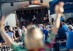 Na zdjęciu panorama sceny z koncertem Muńka i Przyjaciół. Na pierwszym planie zamazana dziewczyna wiwatująca na cześć artysty