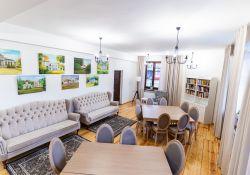 Pomieszczenie, biała ściana, pod nią dwie jasne kanapy, drewniana podłoga, na środku dwa stpły, wokół nich krzesła, na ścianach obrazy, jasne zasłonki, pod kolejną ścianą biała szafka